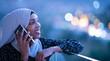 Leinwanddruck Bild - Young Muslim woman on  street at night using phone