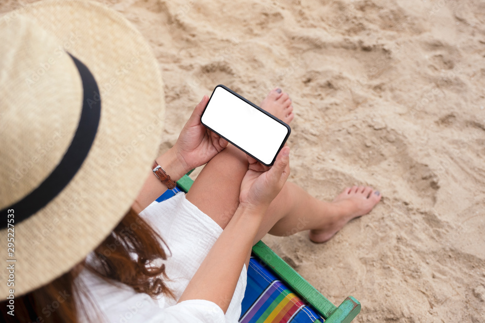 Fototapety, obrazy: Mockup image of a woman holding black mobile phone with blank desktop screen while sitting on a beach chair