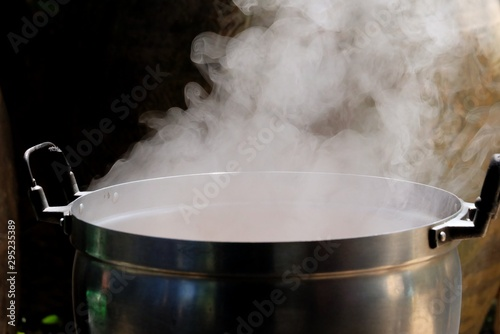 Fotomural  White smoke from a hot cooking pot in kitchen area with dark background