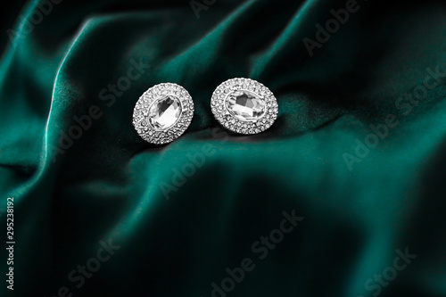 Fotomural  Luxury diamond earrings on dark emerald green silk, holiday glamour jewelery pre