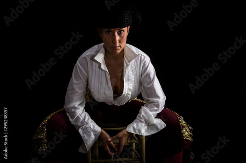 Woman bullfighter sitting on a wooden chair holding a rosary