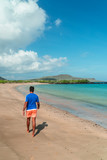 Man walking on Galapagos beach. Tourist man walking along Tropical beach with turquoise ocean waves and white sand. Sand bay view. Holiday, vacation, paradise, summer vibes. Shot in Isabela, San Crist
