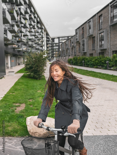 fototapeta na szkło City bike Asian girl happy riding bicycle commuting outside condo apartment building street.