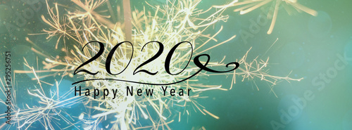 Fototapeta New Year banner, header for social media. Scales down to fit a facebook header size. Sparklers against a background with bokeh and falling snow effect. Happy New Year 2020 quote. obraz