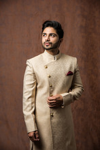 Indian Bridegroom Wears Ethnic Or Traditional Kurta / Cloths.  Male Fashion Model In Sherwani, Posing / Standing Against Brown Grunge Background, Selective Focus