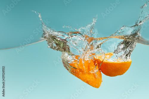 Fototapeta owoce w wodzie   dojrzale-polowki-pomaranczy-wchodzacych-w-wode-z-plamami-na-niebieskim-tle