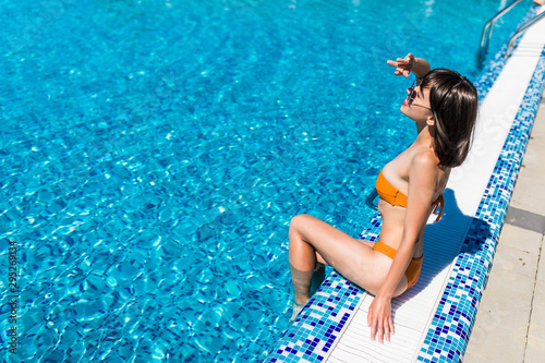 Fotografie, Tablou  Young woman sitting on the edge of the pool.