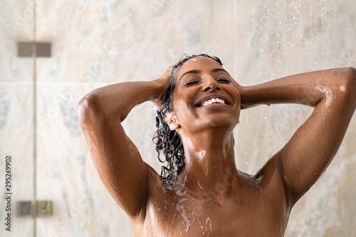 Fotografia African woman washing hair under shower