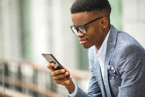 Fotomural  handsome young african man in a suit with a phone in his hand