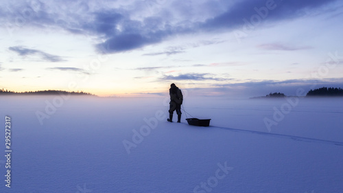 Fotografia  Man silhouette walk on the ice surface covored by snow at evening