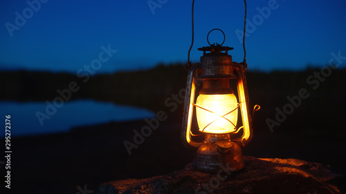 Photo  Gasoline lantern on a rock in the deep forest near lake at night.