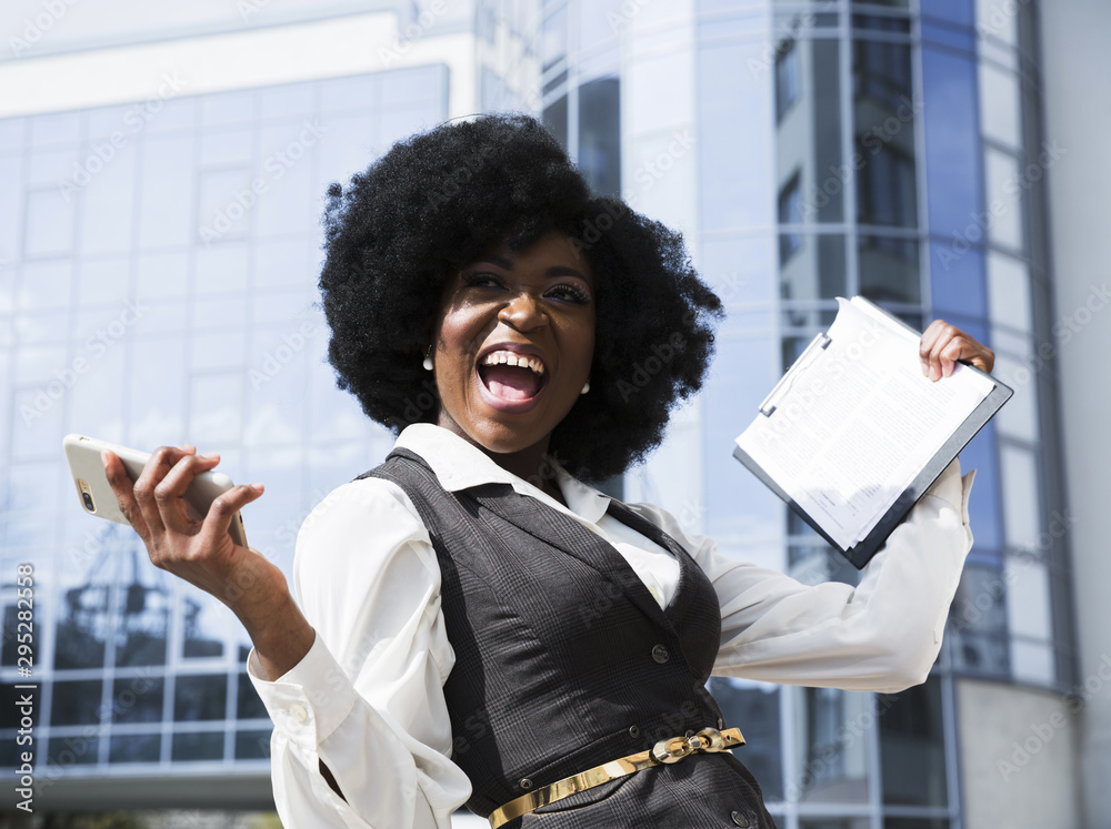 Fototapeta Excited young african businesswoman holding mobile phone and clipboard