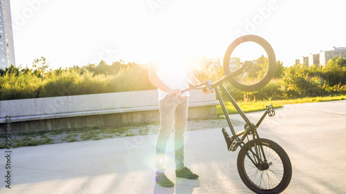 Photo Unrecognizable young BMX rider in park s holding up BMX bicycle on sunny summer