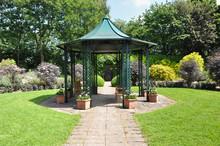 Large  Hexagonal Gazebo Provides Shade For Seating InEnglish Formal Garden