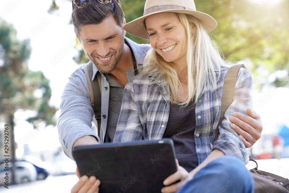 Fototapety, obrazy: Couple of tourists using digital tablet in town