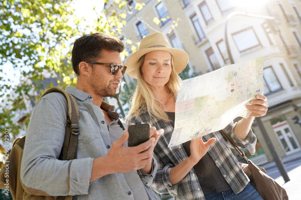 Fototapety, obrazy: Couple of tourists scanning information on city map