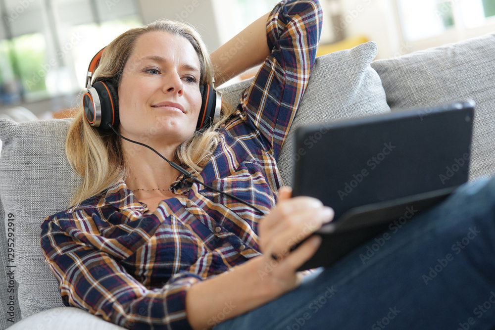 Fototapety, obrazy: Blond woman relaxing in sofa, watching movie on tablet