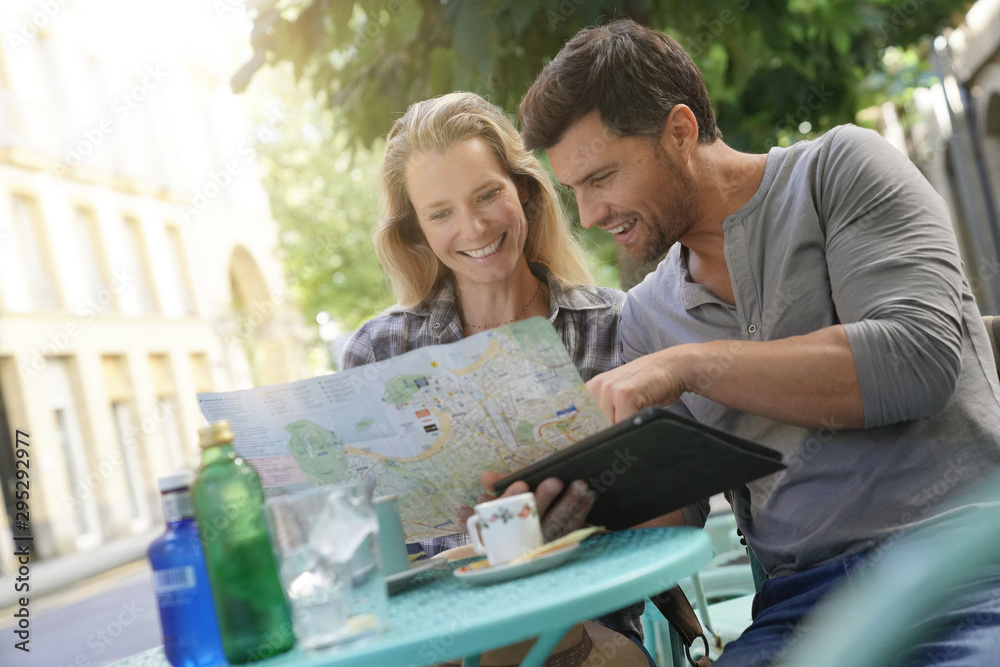 Fototapety, obrazy: Tourists sitting at coffee shop table reading map