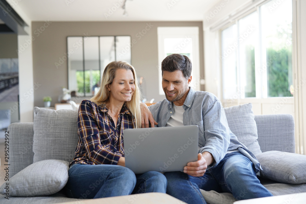 Fototapety, obrazy: Cheerful couple at home using laptop