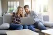 Leinwanddruck Bild - Cheerful couple at home using laptop