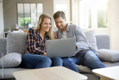 Fotografie, Obraz Cheerful couple at home using laptop