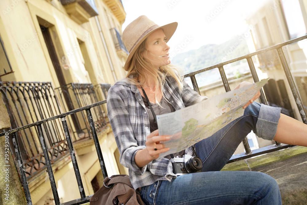 Fototapety, obrazy: Beautiful blond woman photographer reading city map
