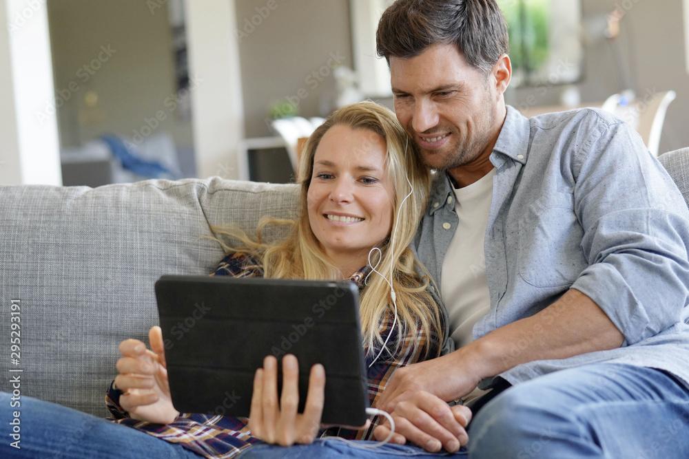 Fototapety, obrazy: Couple watching movie on digital tablet, using earphones