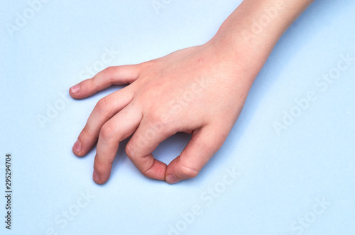 symbol alright shown by child's hand on blue paper background Wallpaper Mural