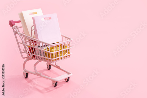 Fotomural Annual sale shopping season concept - mini pink shop cart trolley full of paper
