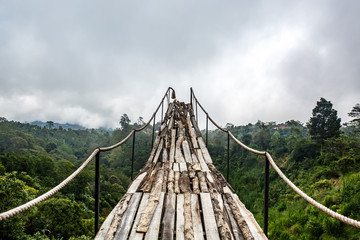 Fototapeta Mosty A wooden bridge over the jungle that breaks off at the end.