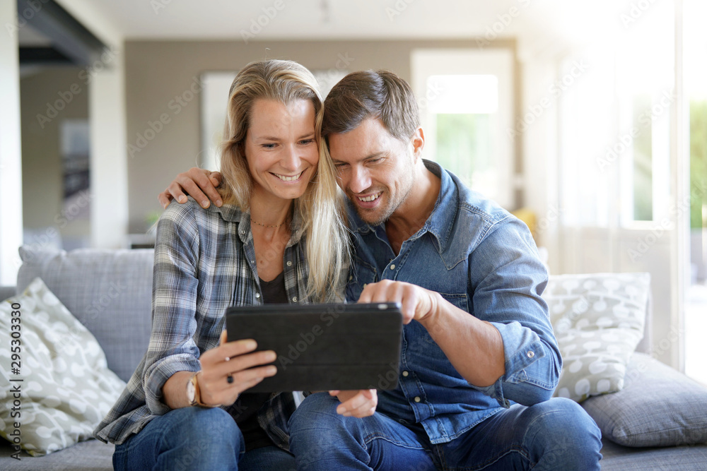 Fototapety, obrazy: Smiling couple at home using digital tablet