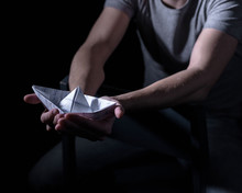 White Paper Boat In The Hands Of An Adult In A Dark Key
