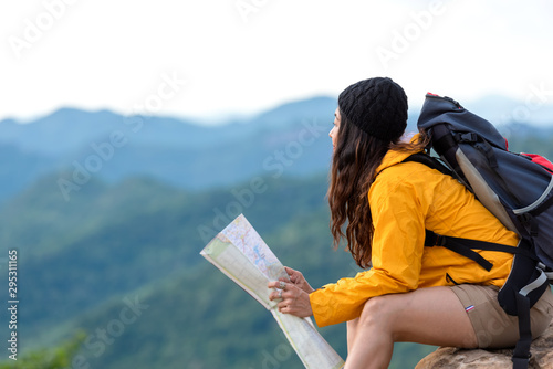 Fotografie, Tablou Asian women hiker or traveler with backpack adventure holding map to find directions and sitting relax on the mountain nature for destination leisure trips