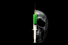 Skull And Syringe With Green Liquid On A Black Background.