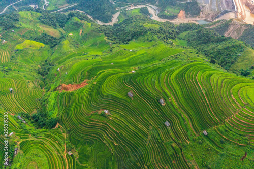 Spoed Fotobehang Rijstvelden Aerial top view of paddy rice terraces, green agricultural fields in countryside or rural area of Mu Cang Chai, Yen Bai, mountain hills valley at sunset in Asia, Vietnam. Nature landscape background.