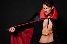 Sexy Man In Vampire Halloween Costume Holding Flogging Whip Isolated On Black