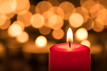 Red Wax Candle Burning In Front Of Bokeh Background