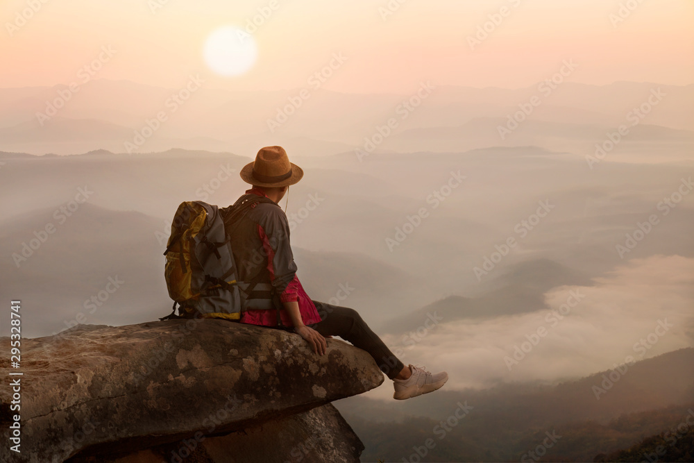 Fototapety, obrazy: Backpacker man sitting on cliff with sunset background