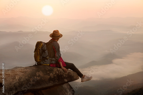 Foto op Plexiglas Cappuccino Backpacker man sitting on cliff with sunset background