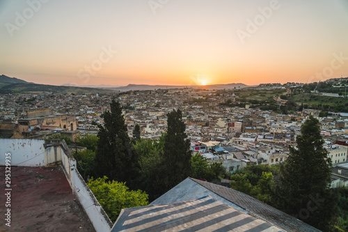 Panoramic scenic view over the roof tops of Medina Fes city at sunrise in Morocco