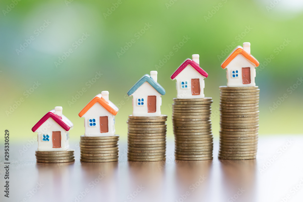 Fototapeta House on the coin, arranged from low to high Concept of starting a business Mortgages and real estate investments Investment for profit
