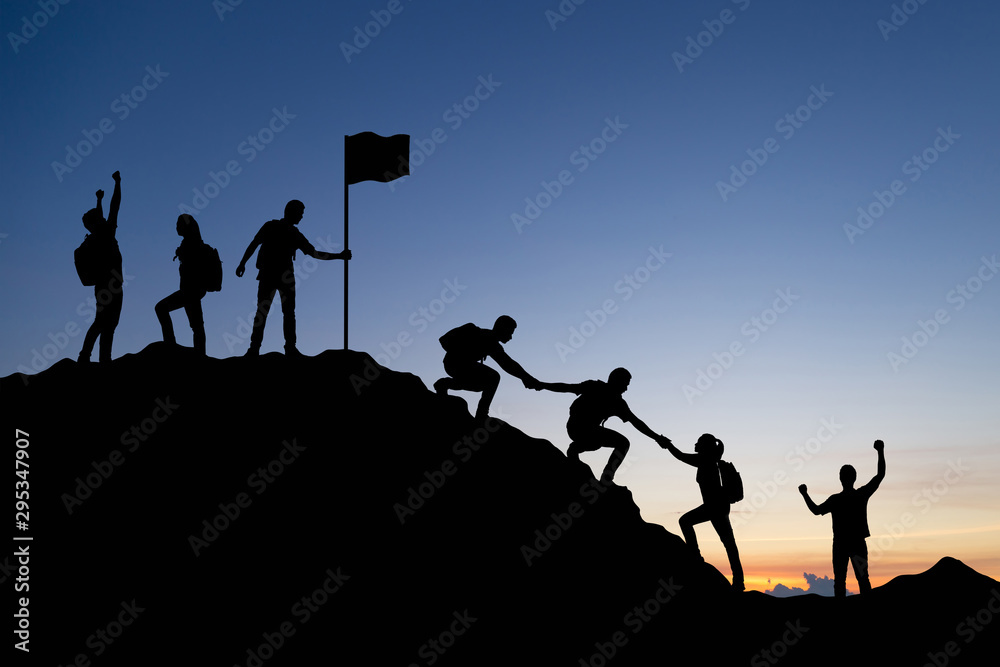 Fototapeta Silhouette of people helping each other hike up a mountain at sunset background. Teamwork, success and goal concept.