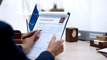 Embassy Employee Checking Visa Application Office, European Union Flag On Table