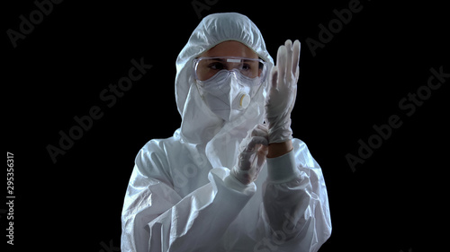 Fototapeta Person in protective suit wearing rubber gloves against dark background, toxins