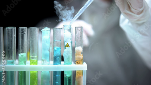 Fotografía Lab worker pouring liquid in test tube with biohazard symbol, modern weapon