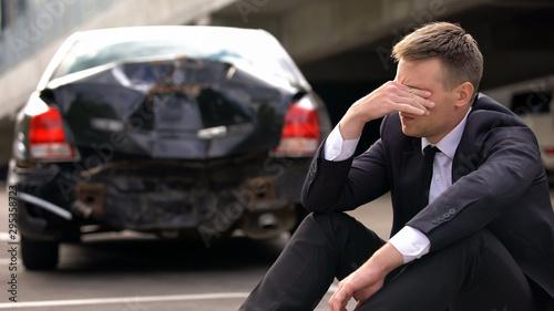 Desperate man sitting asphalt on crashed car background, automobile accident Canvas Print