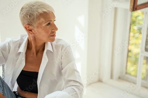 Cuadros en Lienzo  Attractive blonde woman looking at the window