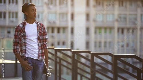Black boy with skate walking alone on street, missing friends, feeling lonely