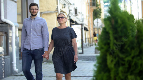 Fotomural  Mature woman walking on street with younger men, relations and connection