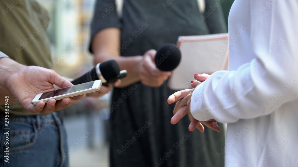 Fototapeta Woman gesticulating during interview with media, press conference, close-up